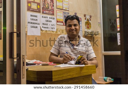 JODHPUR, INDIA - 16 FEBRUARY 2015: Indian man sits in Gold loan office and writes on notebpad. - stock photo