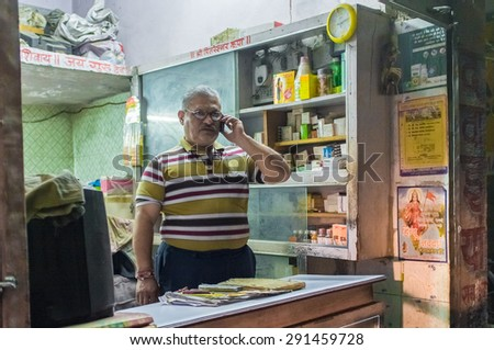 JODHPUR, INDIA - 16 FEBRUARY 2015: Local pharmacists talks on cell-phone before closing time. - stock photo