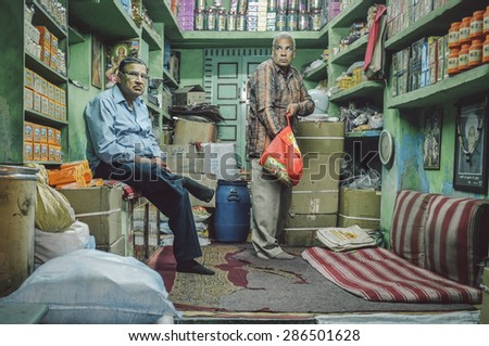 JODHPUR, INDIA - 07 FEBRUARY 2015: Shop owner waiting while customer looks for goods to buy. Shop owners also stay in stores until late working hours.Post-processed with added grain and texture. - stock photo