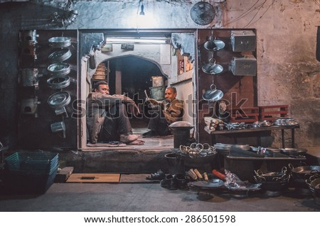 JODHPUR, INDIA - 16 FEBRUARY 2015: Two workers sit and rest before closing time. Stores with kitchen pottery made from metal are common on Asian markets. Post-processed with grain and texture. - stock photo