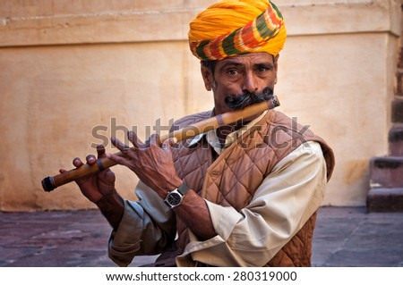 JODHPUR, INDIA - FEBRUARY 28, 2013: Undefined man wearing turban playing on the flute in the Jodhpur fort, India. February 28, 2013