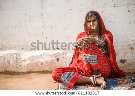 Jodhpur, India - 2015, January 2 : A woman belonging to the Bishnoi tribe posing in front of a white wall in a village near to Jodhpur in central Rajasthan, India