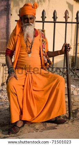 JODPUR, INDIA-CIRCA JANUARY 2008 : A bearded Holy Man in traditional orange robes sits outside the market in Jaipur, India, to give blessings to passers by circa January 2008 in Jodpur, India.