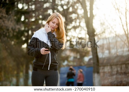 Jogger girl with earphones in sportswear using her smartphone before morning jogging practice on the street - stock photo