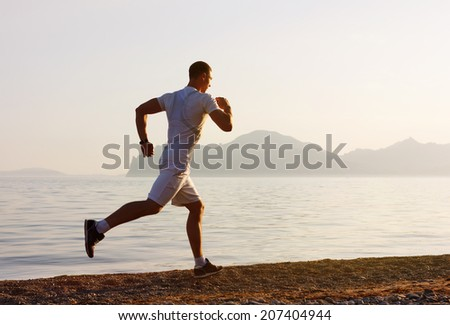 Jogger  in fitness clothing running along beach coast with the blue sky in the background and open space around him - stock photo