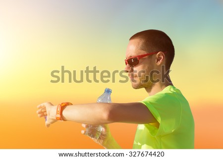Jogger making a pause in the park and checking his running time. - stock photo
