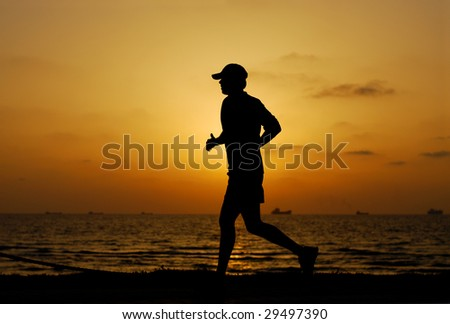 Jogger on a beach at sunset - stock photo