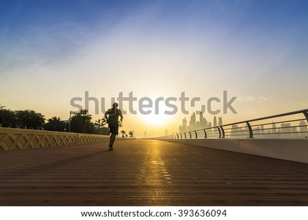 jogger on an empty boardwalk running against the sun with the skyline of Dubai in the background, UAE, Middle East - stock photo