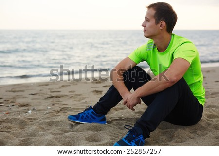Jogger resting after run sitting on the sand and enjoying amazing sunset view, athlete taking break after training outdoors in amazing landscape, man relaxing outdoors