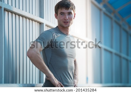 Jogger resting after running. Man runner taking a break during training outdoors in city. Young Caucasian male fitness model after work out. - stock photo
