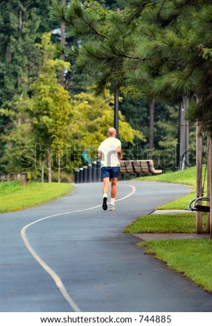 Jogger running down a running trail - stock photo
