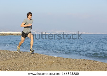 Jogger running fast on the beach near the sea with a city in the background