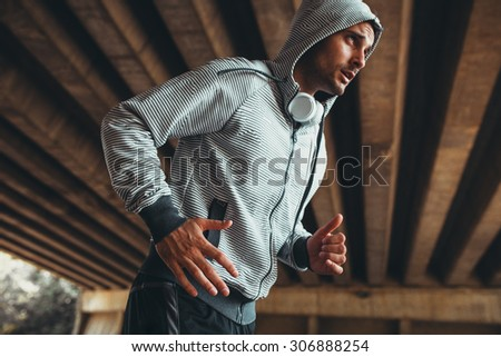 Jogger running in city environment.He wearing headphones around neck. - stock photo