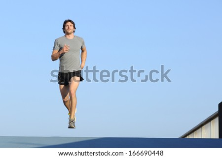 Jogger running towards camera on blue with the horizon in the background           - stock photo