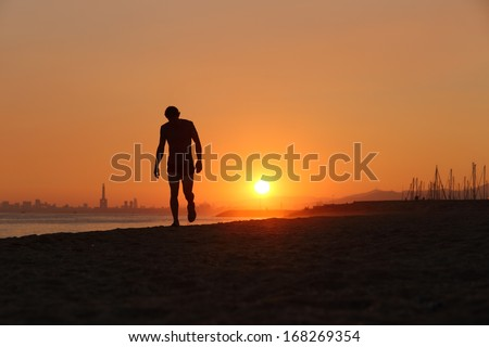 Jogger silhouette walking exhausted after a hard training at sunset - stock photo