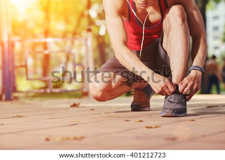 Jogger tying shoe laces before jogging