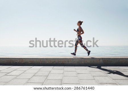 Jogging athlete young woman running at sea background. Fitness runner training outside by the ocean sea in beautiful sunset or sunrise in sports clothing in summertime. - stock photo