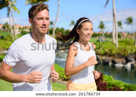 Jogging couple of runners running together in park. Active summer lifestyle, two young adults joggers cardio training in city park or street living healthy. - stock photo