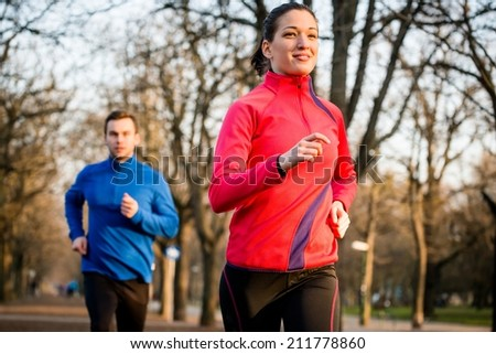 Jogging couple - young man and woman competing, woman first - stock photo