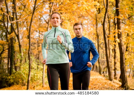 Jogging couple - young man and woman competing, woman first
