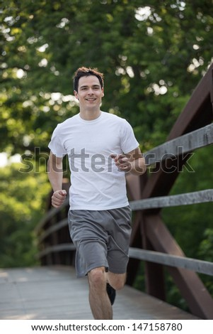 Jogging Healthy Looking Young Man Cross Bridge Under Morning Sunlight - stock photo