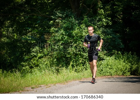 Jogging in nature - young man training with barbells - stock photo