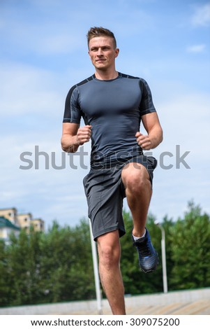 Jogging man on the stadium. Close up vertical shot