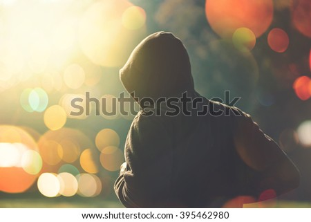 Jogging outdoors on autumn morning, hooded man running in the park, retro toned image with selective focus and bokeh light - stock photo