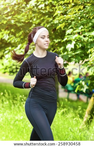 Jogging Theme: Happy Smiling Caucasian Sportswoman Having Jogging Exercises Outdoors. Vertical Image - stock photo