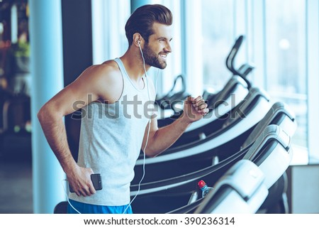 Jogging with pleasure. Side view of young handsome man in headphones looking away with smile while running on treadmill at gym - stock photo