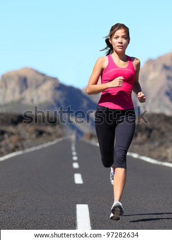 Jogging woman running. Female runner during outdoor workout in beautiful mountain nature landscape. Beautiful young mixed race fit fitness model training for marathon. - stock photo