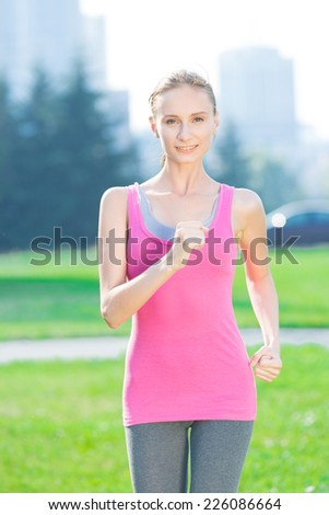 Jogging woman running in city park in sunshine on beautiful summer day. Sport fitness model caucasian ethnicity training outdoor for marathon. - stock photo