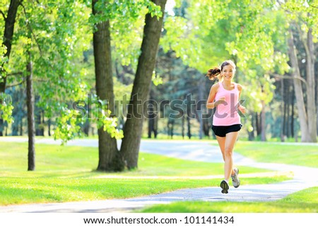 Jogging woman running in park in sunshine on beautiful summer day. Sport fitness model of mixed Asian / Caucasian ethnicity training outdoor for marathon. - stock photo