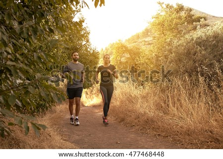 Jogging young couple in shadows with sun light behind them while wearing black and grey jogging attire