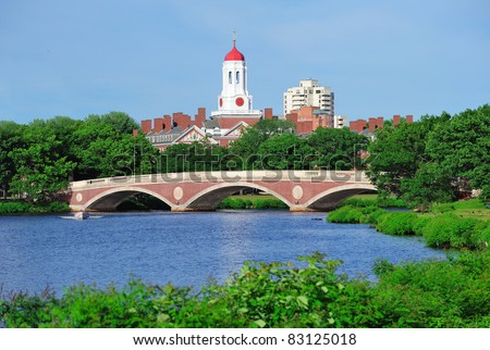 John W. Weeks Bridge and clock tower over Charles River in Harvard University campus in Boston with trees and blue sky.