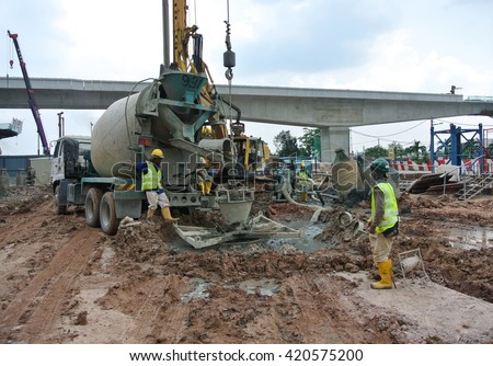 JOHOR, MALAYSIA -APRIL 01, 2015: Bore pile concreting work at construction site. Wet concrete pour or pump from the concrete lorry into the bore pile casing.