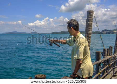 Johor, Malaysia-April 16, 2017:Fisherman throwing bite  at Kelong Aceh,Johor.Kelong is a form of offshore platform built predominantly for fishing.Image contain  noise and soft focus