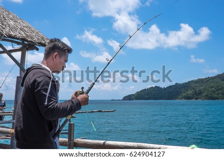 Johor, Malaysia-April 16, 2017:Fisherman with his fishing pole  at Kelong Aceh,Johor.Kelong is a form of offshore platform built predominantly for fishin purposes.Image contain  noise and soft focus