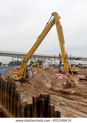 JOHOR, MALAYSIA -JANUARY 02, 2016: Excavators machine is heavy construction machine used to do soil excavation work at the construction. Powered by long hydraulic arm with basket. Handle by workers.