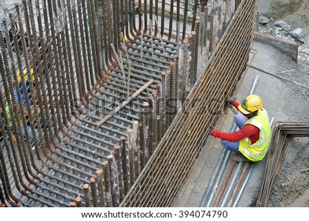 JOHOR, MALAYSIA - MARCH 03, 2015: Construction workers fabricating pile cap steel reinforcement bar at the construction site.   - stock photo