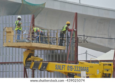 JOHOR, MALAYSIA -MAY 15, 2016: Construction workers standing in the mobile crane bucket while working at high level in the construction site in Malaysia.  - stock photo
