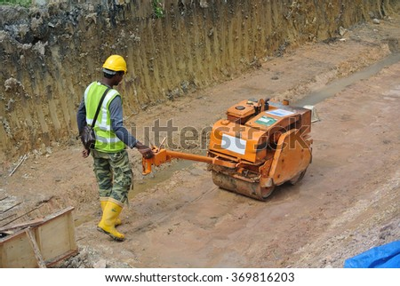 JOHOR, MALAYSIA � SEPTEMBER 25, 2014: Construction workers using baby roller compactor to compact soil at the construction site in Johor, Malaysia on September 15, 2014.