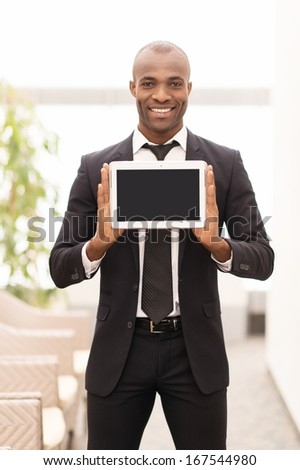 Join a digital age. Cheerful young African man in formalwear showing a screen of digital tablet and smiling at camera - stock photo