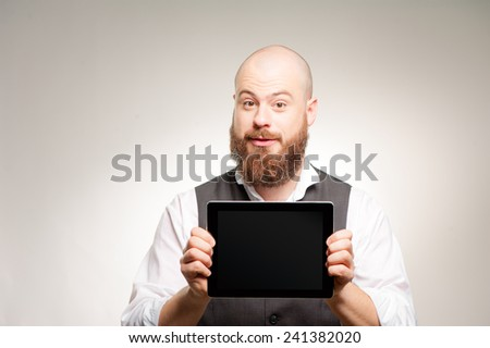 Join a digital age. Cheerful young bearded man showing a screen of digital tablet and smiling at camera - stock photo
