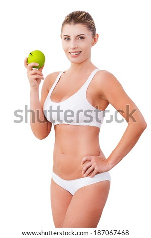 Join a healthy lifestyle! Beautiful mature woman in underwear holding a green apple and smiling while standing isolated on white - stock photo