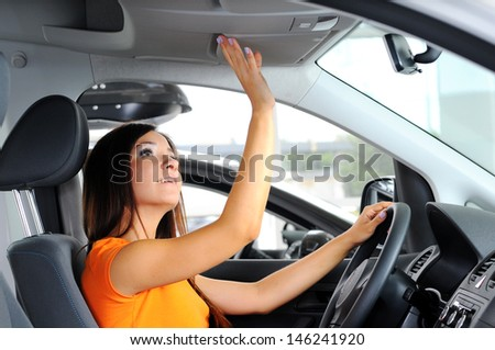 Join me for a drive. Attractive young woman sitting at the front seat of the car looking at camera