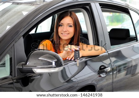 Join me for a drive. Attractive young woman sitting at the front seat of the car looking at camera - stock photo