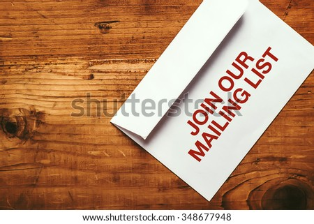 Join our mailing list imprint stamp on white paper envelope placed on top of office desk, top view - stock photo
