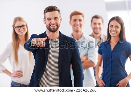 Join our team! Beautiful young woman showing her thumb up and smiling while group of happy young people standing on background and smiling - stock photo