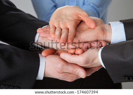 Joined hands of business people - closeup shot - stock photo